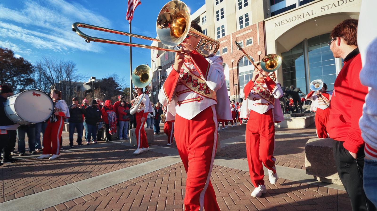 people in red and white uniform playing musical instruments on street during daytime