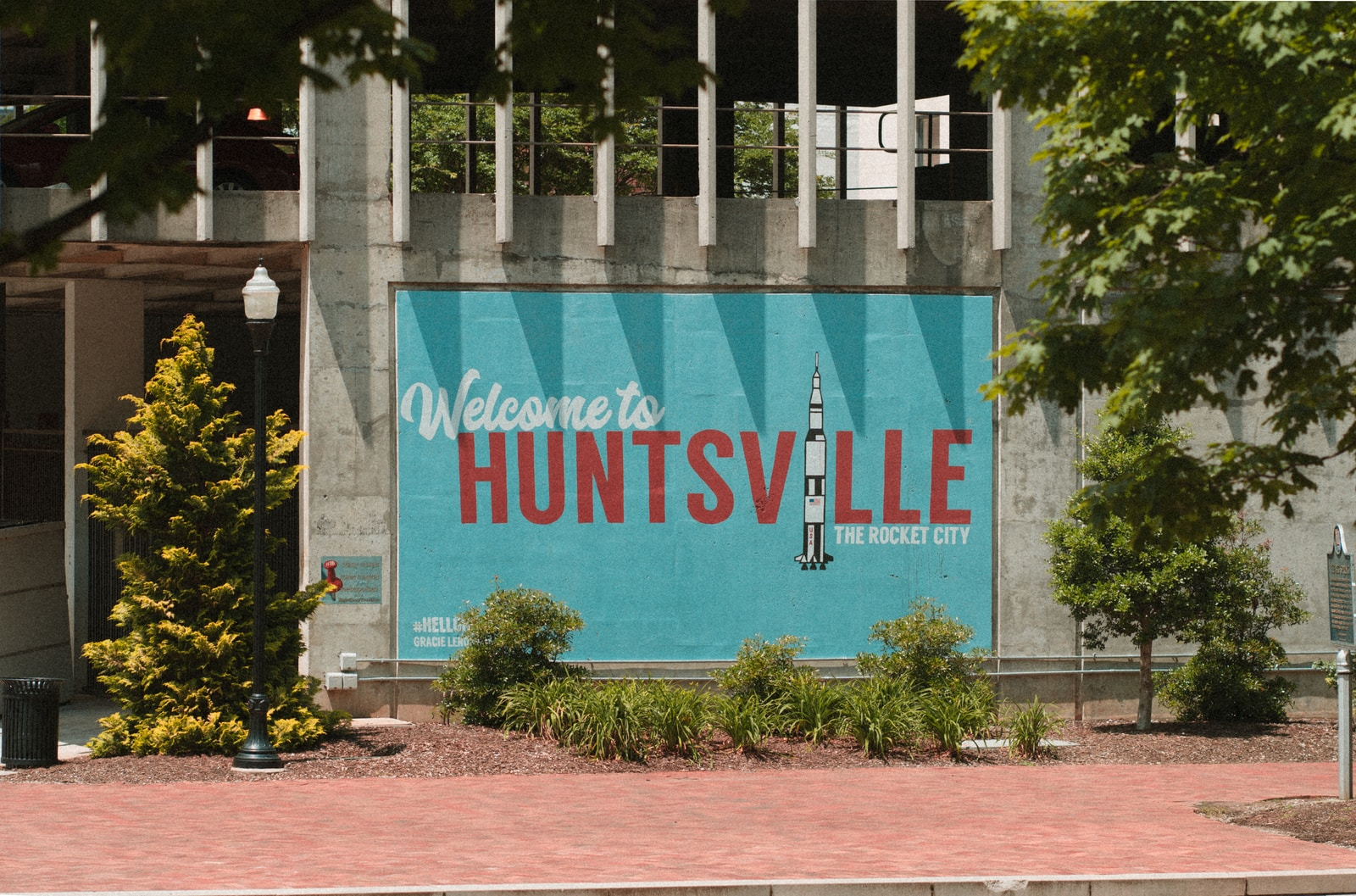 welcome to Huntsville sign on wall near trees and lamppost